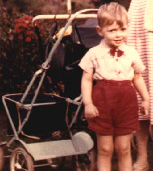 Baby Nelson standing by his pram in a London park