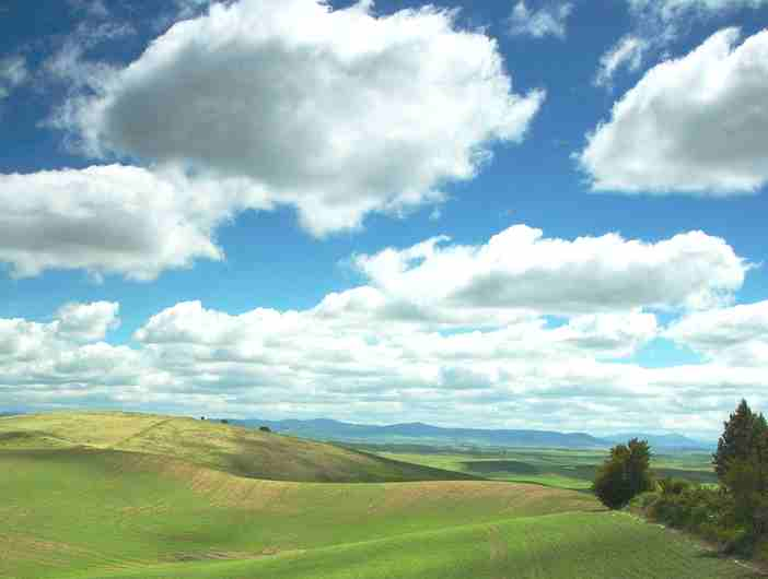 Clouds over rolling green hills