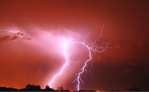 Lightning illuminates the night sky red