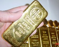Gold bars or ingots with Krugerrands in the background.