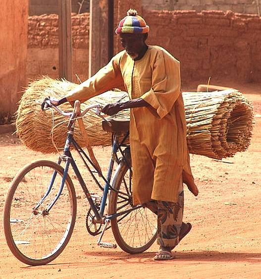 Using a bicycle for transport, typical indian and african daily picture of sustainability