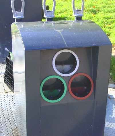 Glass waste collection point in a neighborhood area for separating clear, green and amber glass - bottle bank